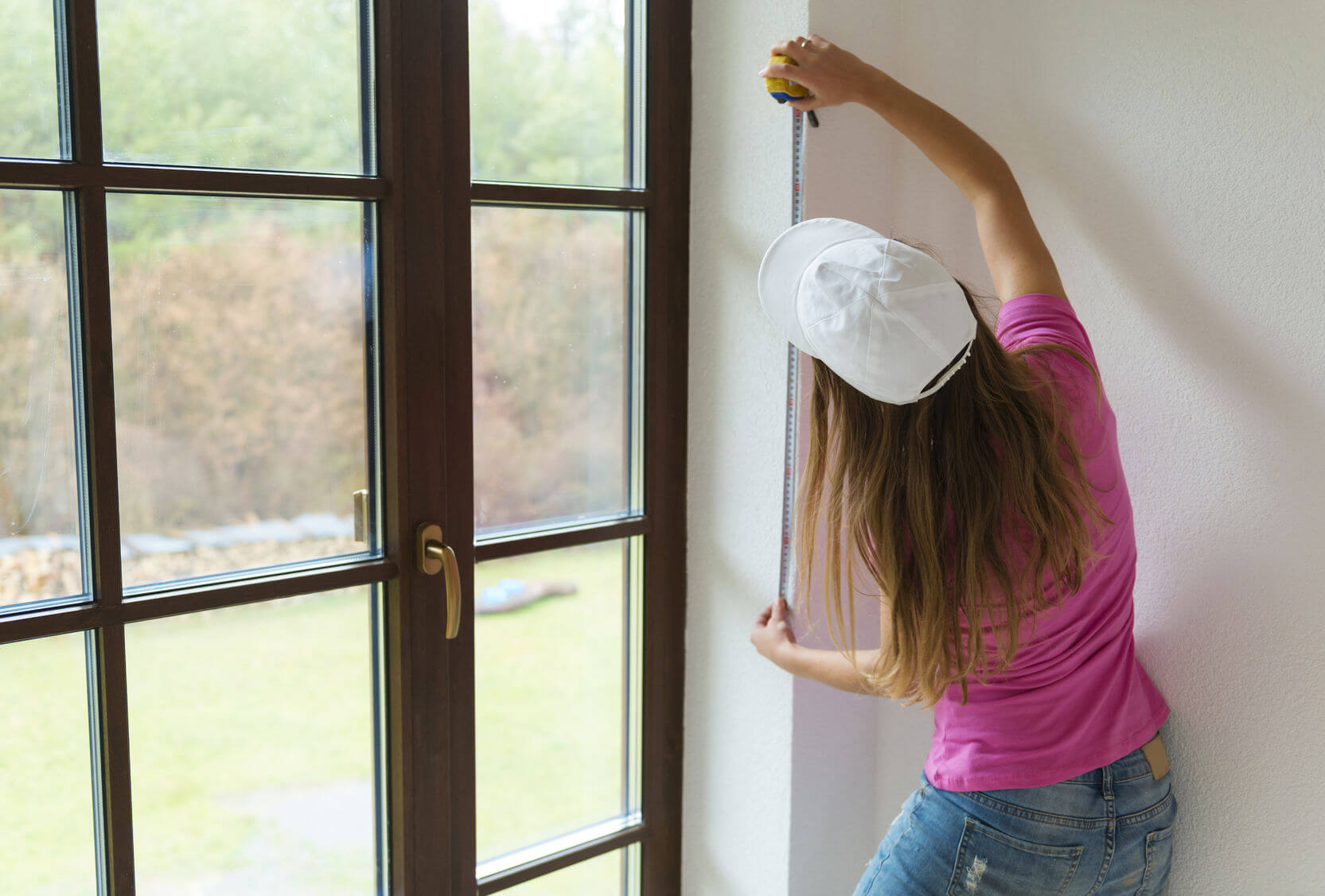 buying curtains or drapes woman measuring window