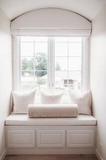 custom made nursery window seat with custom made roman shade and pillows